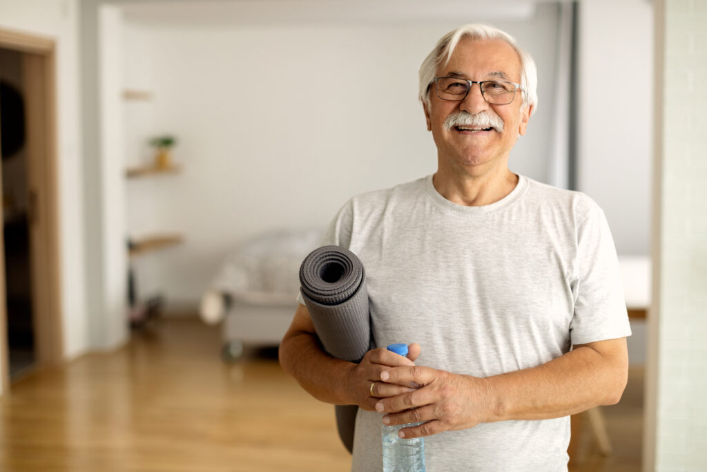 a man with arthritis ready to exercise with yoga mat